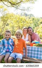 Portrait of happy family sitting at table in park