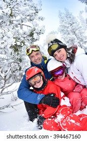 Portrait of happy family of skiers in snowy mountain