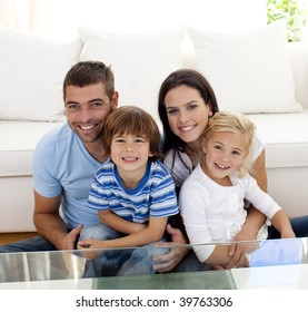 Portrait of happy family smiling at the camera in living-room