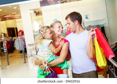 Portrait of happy family spending free time in department store