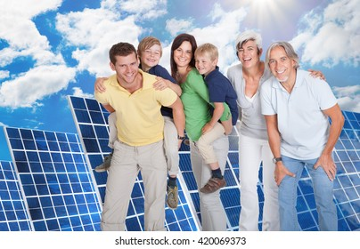 Portrait Of A Happy Family Standing Against Solar Panel