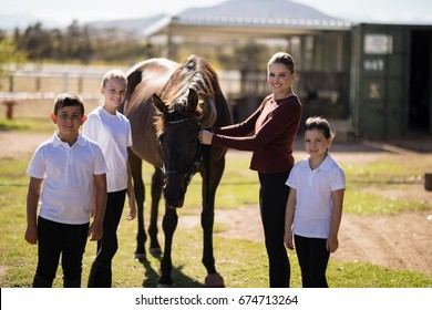 Portrait of happy family standing with a brown horse in the ranch