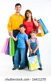 Portrait of happy family standing and holding bags while looking at camera with smiles