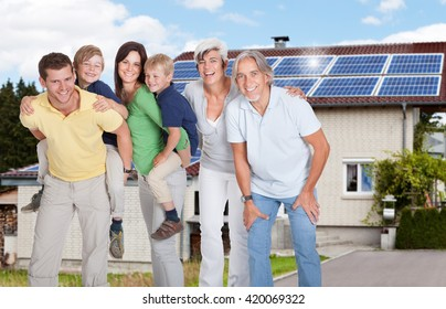 Portrait Of A Happy Family Standing Outside Their House With Solar Panels Fitted On Roof