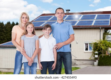 Portrait Of A Happy Family Standing Outside Their House With Solar Panels On Roof