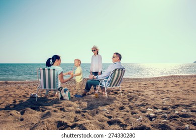 Portrait of a happy family in summer nature. Mother and father are sitting on a beach deck chair, daughter and son playing