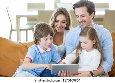 Portrait of happy family with two children sitting on sofa and using digital tablet pc