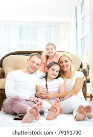 Portrait of happy family with two children sitting at home