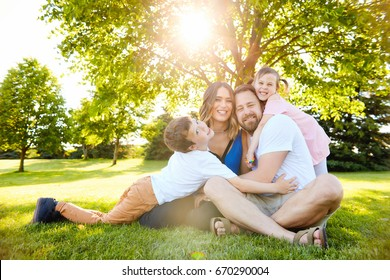 Portrait of happy family with two little children resting together in summer park, embracing, looking at camera and smiling