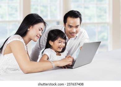 Portrait of happy family using laptop computer together at thome while smiling happy