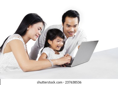 Portrait of happy family using laptop computer together on the table, isolated on white background