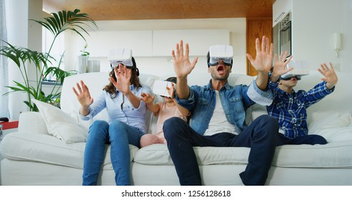 Portrait of happy family using vr glasses in living room in slow motion. Concept of innovation technology, family entertainment, game