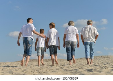 Portrait of a happy family a walking barefoot in the sand in the summer
