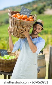 Portrait of happy farmer carrying by fresh oranges in container at farm market for sale