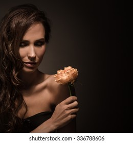 Portrait of happy fashion model in nirvana posing in photo studio. Beautiful lady with long brown hair holding orange rose and looking down.