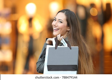 Portrait of a happy fashion shopper looking at camera in a store