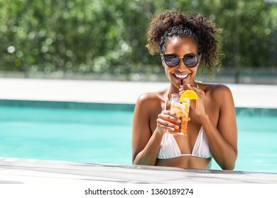 Portrait of happy fashion woman with sunglasses standing in swimming pool drinking cocktail. Beautiful african glamour girl with fresh soft drink for appetizer in luxury pool looking at camera.