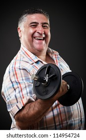 Portrait of a happy fat man with dumbbell on gray background