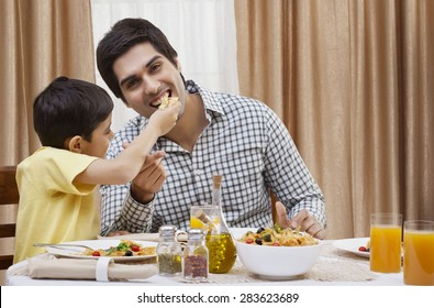 Portrait of a happy father being fed a piece of pizza by his son