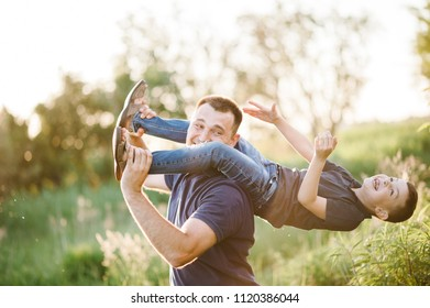 Portrait of happy father carrying on shoulders son on summer vacation. Father's Day. Dad and son playing in the park at the sunset time. People having fun on field. Concept of friendly family. Closeup