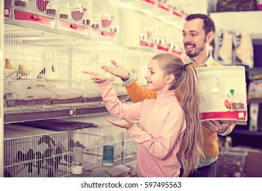 Portrait happy father and daughter choosing pretty bird for keeping in pet shop