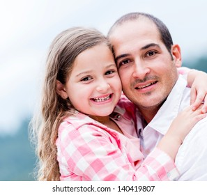 Portrait of a happy father and daughter smiling outdoors