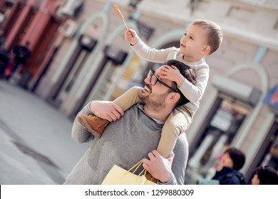 Portrait of happy father giving son piggyback ride on his shoulders.