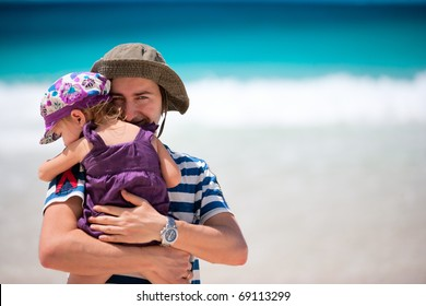 Portrait of happy father and his adorable little daughter at beach