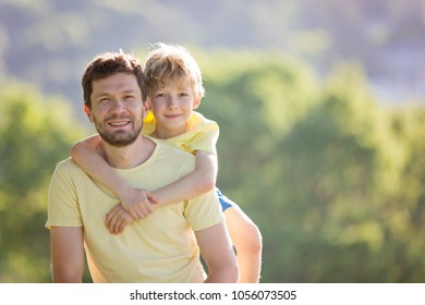 portrait of happy father and his little son, son hugging his father, father's day concept, copy space on right