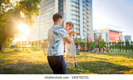 Portrait of happy father hugging and spinning his smiling little toddler son in park