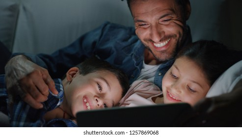 Portrait of happy father and kids using a tablet on sofa in the evening. Concept of family entertainment, education, technology
