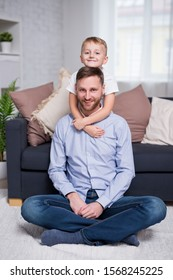 portrait of happy father and little son sitting in modern living room at home