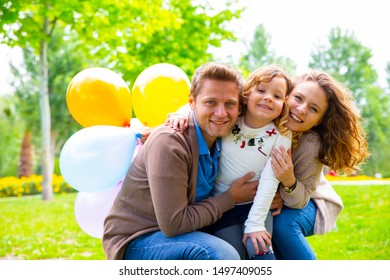 Portrait of happy father, mother and daughter having fun playground