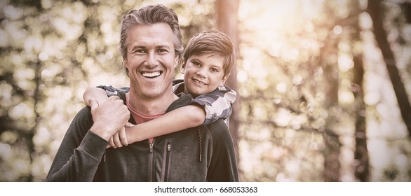 Portrait of happy father piggybacking son while hiking in forest
