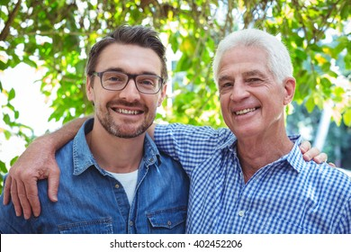 Portrait of happy father and son with arm around while standing outdoors