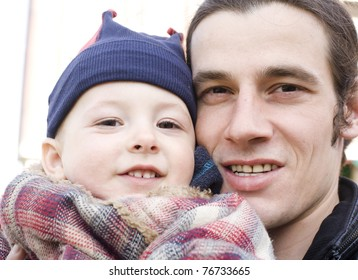 portrait of happy father with son hugging outside