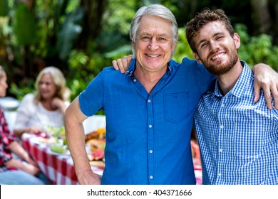 Portrait of happy father and son standing in yard