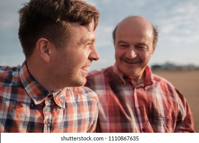portrait of happy father and son walking outdoors. They look on each other. Concept of good releationship between generations