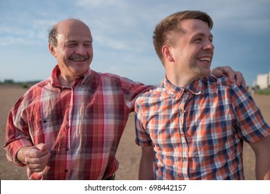 portrait of happy father and son walking outdoors. They look aside to the right