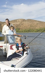Portrait of a happy father with sons fishing in boat on lake