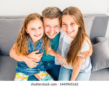 Portrait of happy father with two adorable smiling daughters on the couch