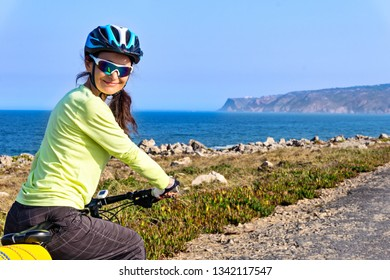 Portrait of  happy femail tourist cyclist on the road  along the ocean shore looking back at the camera and smiling. Portugal, Europe.