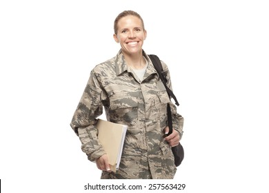 Portrait of happy female airman with shoulder bag and books against white background