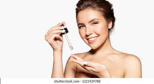 Portrait of happy female applying cosmetic oil on hand. Sincere smile of pretty woman posing in studio. Beauty skincare concept. Isolated on grey background