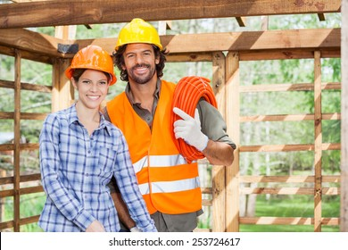 Portrait of happy female architect standing with construction worker in incomplete wooden cabin at site