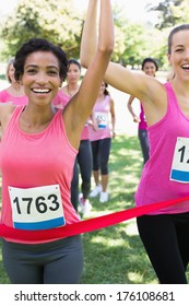 Portrait of happy female breast cancer participants winning marathon race at park