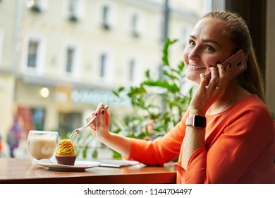 Portrait of happy female business woman  has fun during leisure time in cafeteria.  Beautiful female is phoning via cell telephone during her leisure time in summer weekend overseas