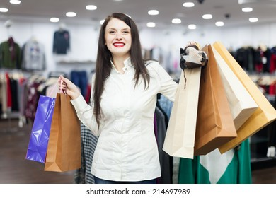 Portrait of happy female buyer with shopping bags