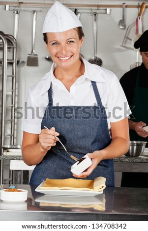 Portrait of happy female chef preparing chocolate roll with colleague in background