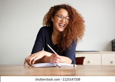 Portrait of happy female college student sitting at desk writing in book
